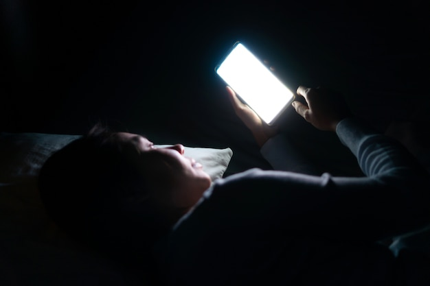 Mooie vrouw in bed met smartphone 's avonds laat in de donkere slaapkamer. mobiele telefoon verslaving concept
