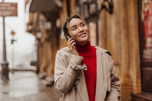 Mooie vrouw in beige jas en felrode top kijkt naar prachtige gebouwen en praten over de telefoon