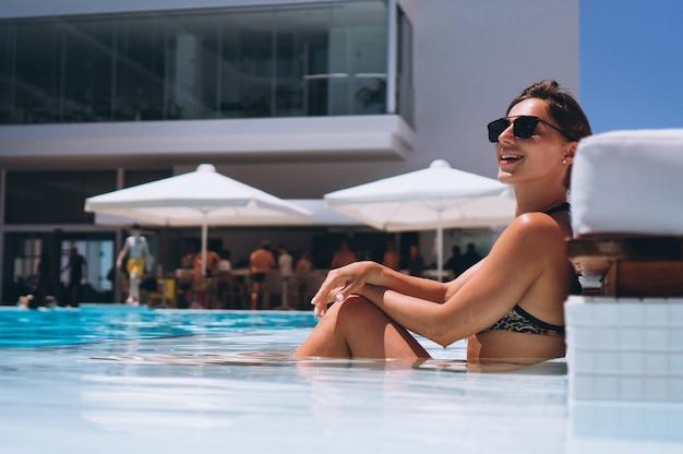 Mooie vrouw in bikini bij het zwembad