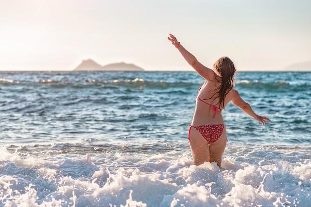 Mooie vrouw in bikini die in de golven van de zee staat en met open armen van de zon geniet