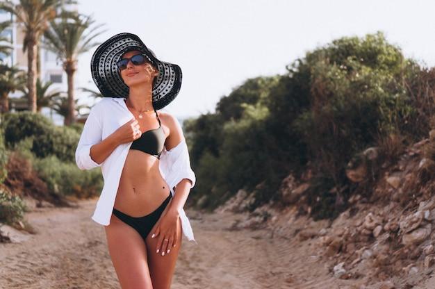 Mooie vrouw in bikini en shirt door palmen
