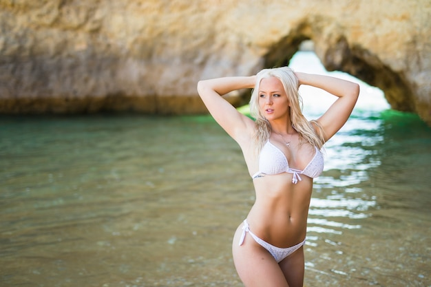 Mooie vrouw in bikini. jong en sportief meisje poseren op een strand in de zomer