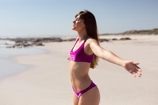 Mooie vrouw in bikini met uitgestrekte armen staande op strand in de zon