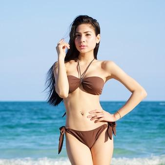 Mooie vrouw in bikini op het strand op zomerdag