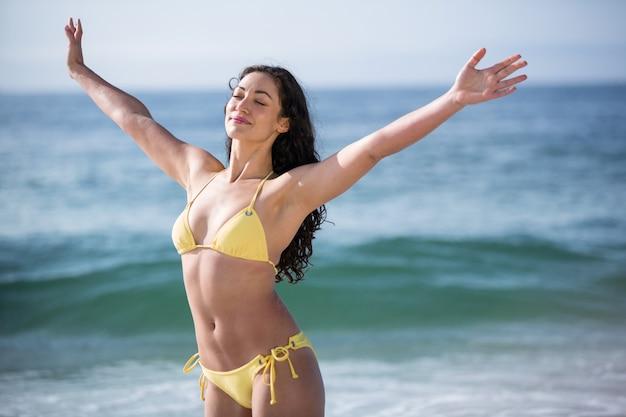 Mooie vrouw in bikini staat met uitgestrekte armen
