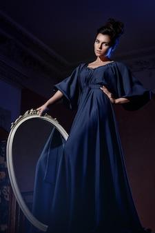 Mooie vrouw in blauwe jurk met een spiegel