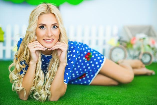 Mooie vrouw in blauwe jurk met witte polka dots, ligt op groen tapijt en houdt handen in de buurt van haar gezicht