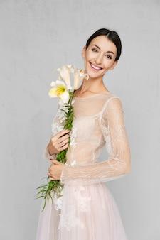 Mooie vrouw in bleke transparante jurk met kant poseren met bloemen in de hand