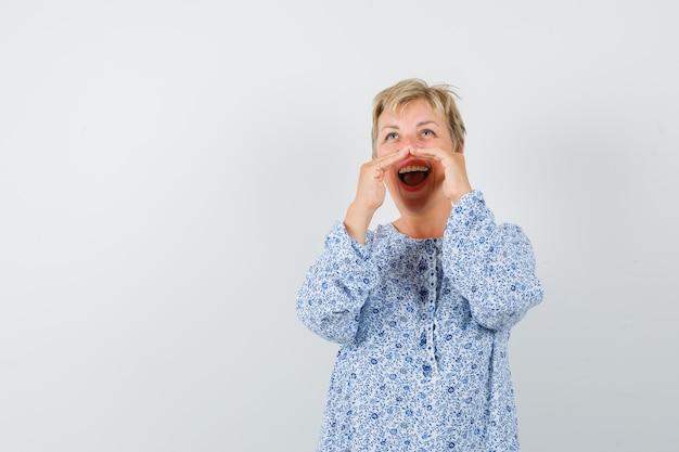 Mooie vrouw in blouse met patroon die onder haar gecombineerde handen schreeuwt en vreugdevol, vooraanzicht kijkt.
