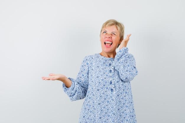 Mooie vrouw in blouse met patroon hoort geluiden terwijl ze haar hand opheft met open handpalm en verbaasd kijkt, vooraanzicht.