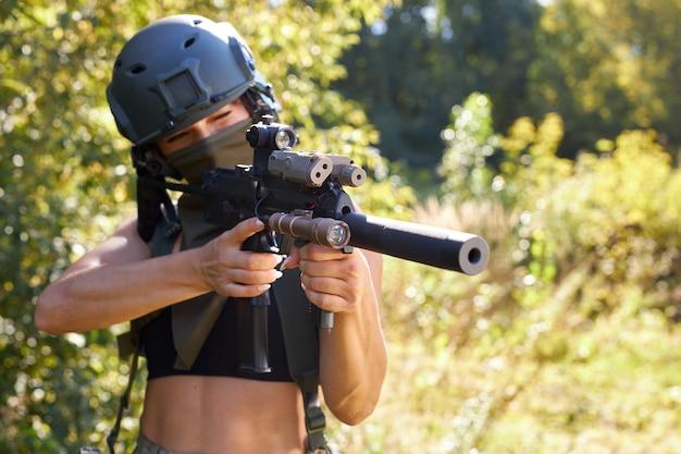 Mooie vrouw in camouflage in haar armen tijdens een oorlog mikt op een doelwit of een vijand