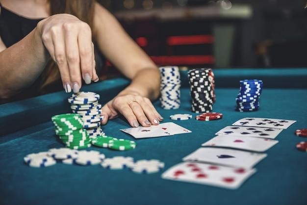 Mooie vrouw in casino die fiches van stapel neemt