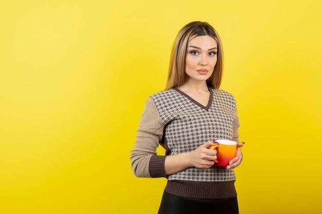 Mooie vrouw in casual outfit met kopje thee.
