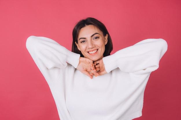 Mooie vrouw in casual witte trui, blij opgewonden bewegen met een glimlach op het gezicht