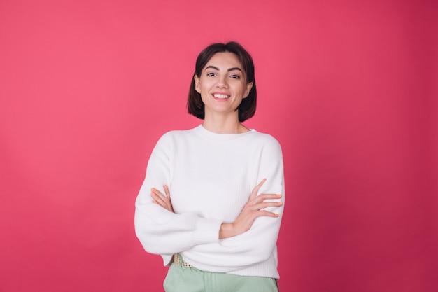 Mooie vrouw in casual witte trui, met gekruiste handen glimlach