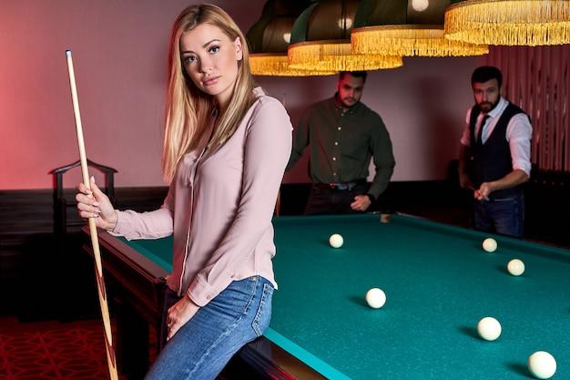 Mooie vrouw in de bar naast biljarttafel pool, mensen die snooker spelen