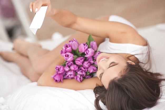 Mooie vrouw in de bedholding bloemen en het lezen van een notitie. jong meisje lacht. vrolijke vrouw met tulpen