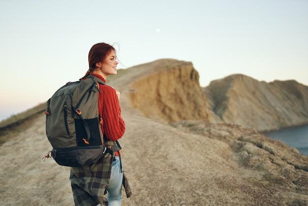 Mooie vrouw in de bergen in de natuur met een rugzak op haar rug in de buurt van de zee