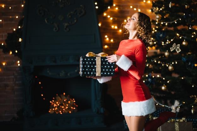 Mooie vrouw in de buurt van een kerstboom met cadeau