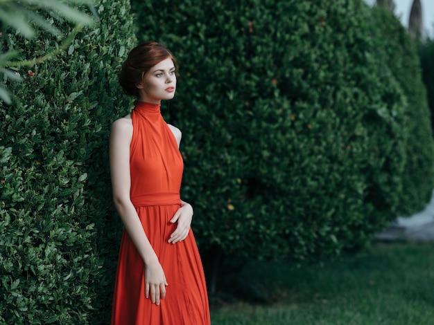 Mooie vrouw in de buurt van struiken rode jurk decoratie fee