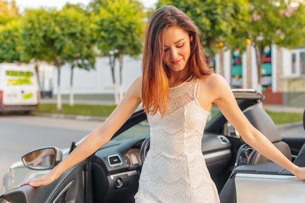Mooie vrouw in de convertibele cabrio-auto op een zonnige dag in een stad