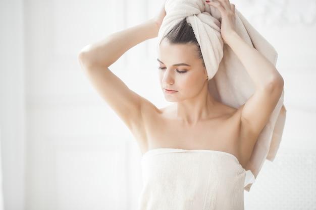 Mooie vrouw in de handdoek na het baden
