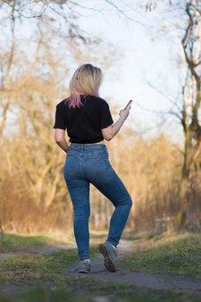 Mooie vrouw in de herfstlandschap. jonge hipster die mobiele telefoon houdt.