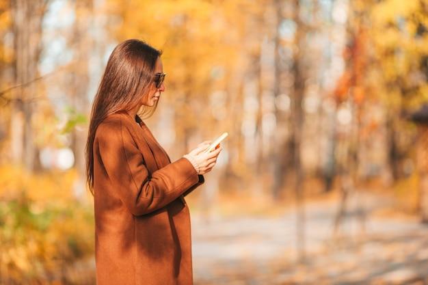 Mooie vrouw in de herfstpark onder dalingsgebladerte