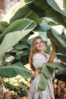 Mooie vrouw in de jungle. een resort of hotel met tropische bomen en planten. vrouw met in de buurt van bananenblad. meisje op vakantie in het regenwoud