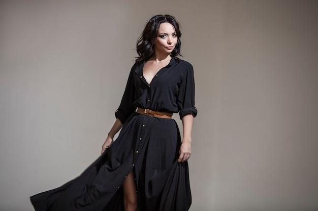 Mooie vrouw in de kamer in de studio danst in een zwarte jurk met lange donkere krullen op zijn hoofd