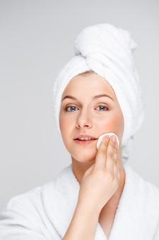 Mooie vrouw in de make-up van de badjassenstart met reinigingsmiddel