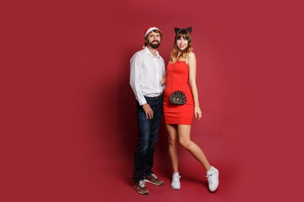 Mooie vrouw in de maskeradehoed van kattenoren en rode korte kleding met haar vriend het stellen op rood. nieuwjaarsfeest. volledige lengte .