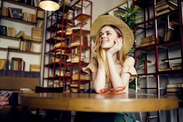 Mooie vrouw in de mededeling van de de bibliotheekvakantie van de elegantiehoed