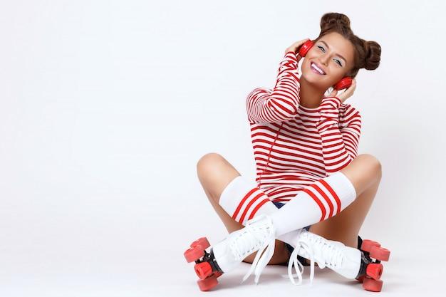 Mooie vrouw in de rolschaatsen en met rode koptelefoon