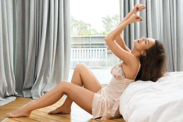 Mooie vrouw in de slaapkamer