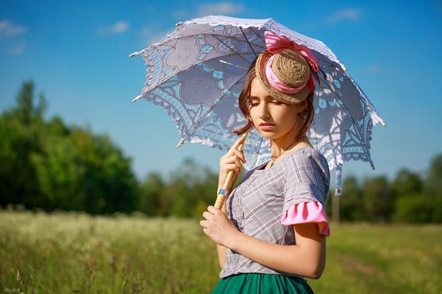Mooie vrouw in de zomer in de natuur met een prachtige paraplu