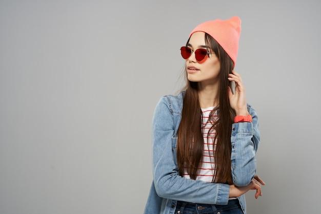 Mooie vrouw in denim shirt zonnebril roze hoed poseren mode grijze achtergrond studio