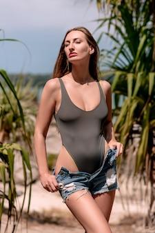 Mooie vrouw in denimborrels en grijze bodysuit