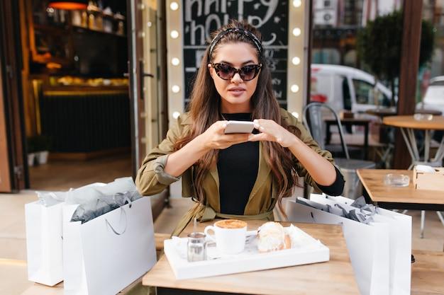 Mooie vrouw in donkere zonnebril zittend op terras naast tassen uit boetiek