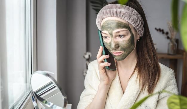 Mooie vrouw in een badjas en met een groen cosmetisch masker op haar gezicht gebruikt haar mobiele telefoon