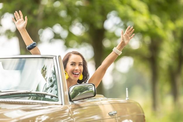 Mooie vrouw in een beige cabriolet met armen boven haar glimlachend in de camera op een zomerse natuurrit.