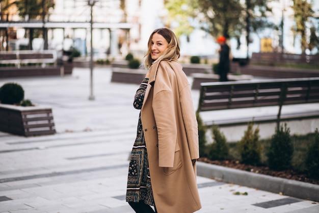 Mooie vrouw in een beige jas buiten in park