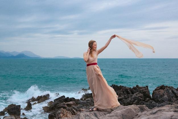 Mooie vrouw in een beige jurk staat op een rotsachtige kust