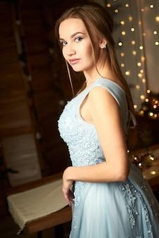 Mooie vrouw in een blauwe avondjurk op een achtergrond van slingers nieuwjaar en kerstconcept