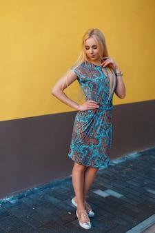 Mooie vrouw in een blauwe jurk met een patroon bij de gele muur