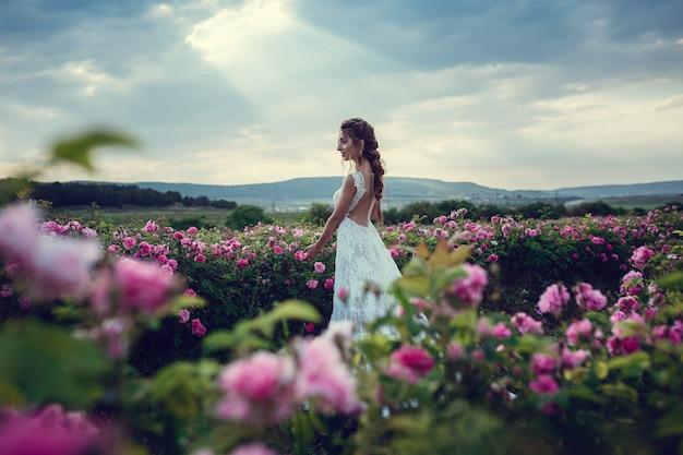 Mooie vrouw in een bloemenpark, tuinrozen. make-up, haar, een krans van rozen. lange trouwjurk. vrouw in boho-stijl