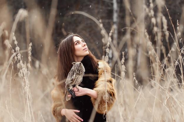 Mooie vrouw in een bontjas met een uil op hand