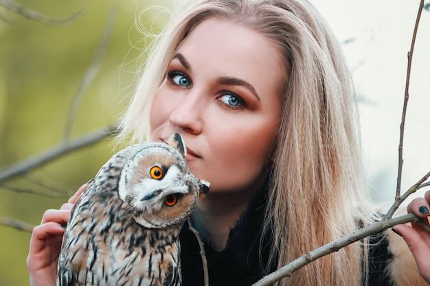 Mooie vrouw in een bontjas met een uil op zijn arm. blonde met lang haar in de natuur met een uil. romantisch delicaat beeld van een meisje