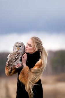 Mooie vrouw in een bontjas met een uil op zijn arm. blonde met lang haar in de natuur met een uil