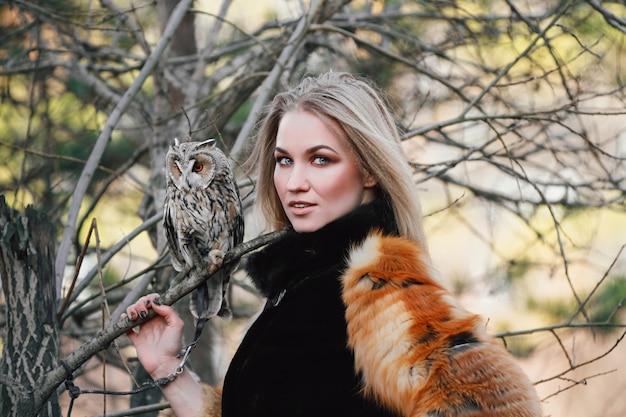 Mooie vrouw in een bontjas met een uil op zijn arm.